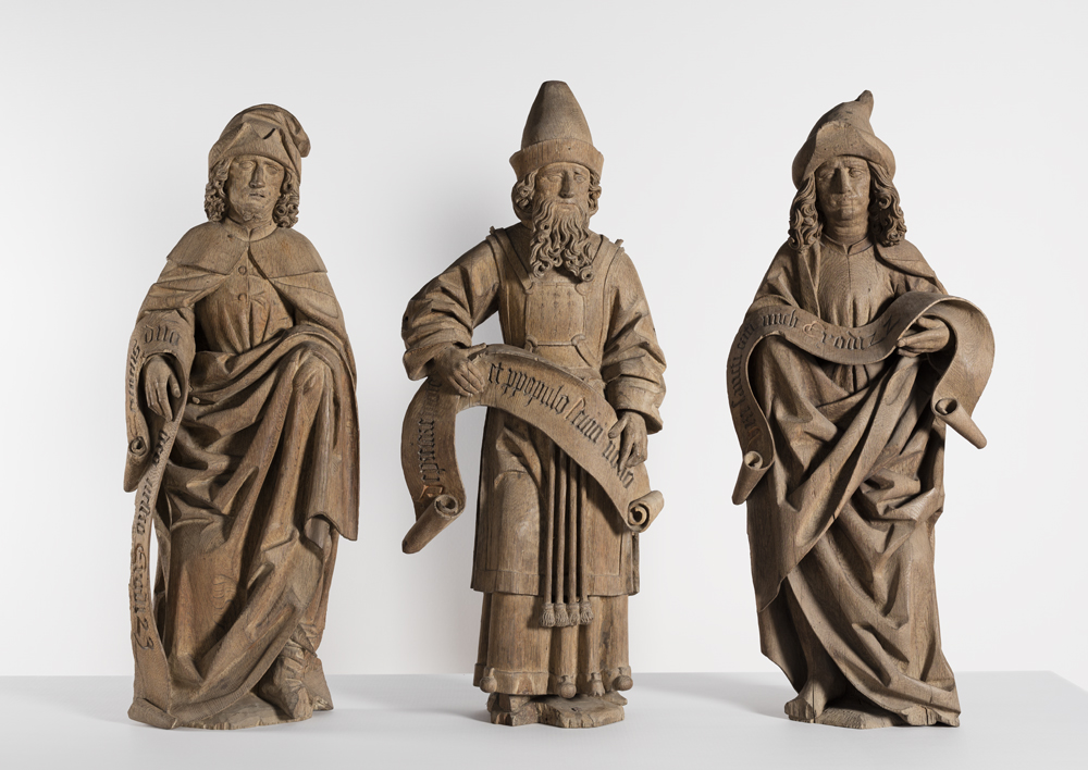 Three male figures in long garments and with caps. Each is carrying a scroll.