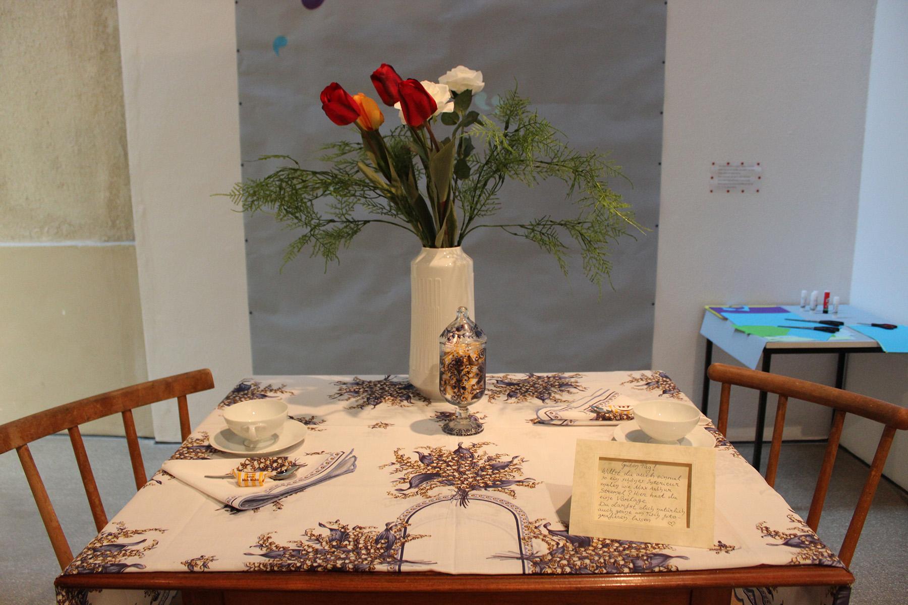 Ein gedeckter Tisch mit Blumenvase und Tischdecke.
