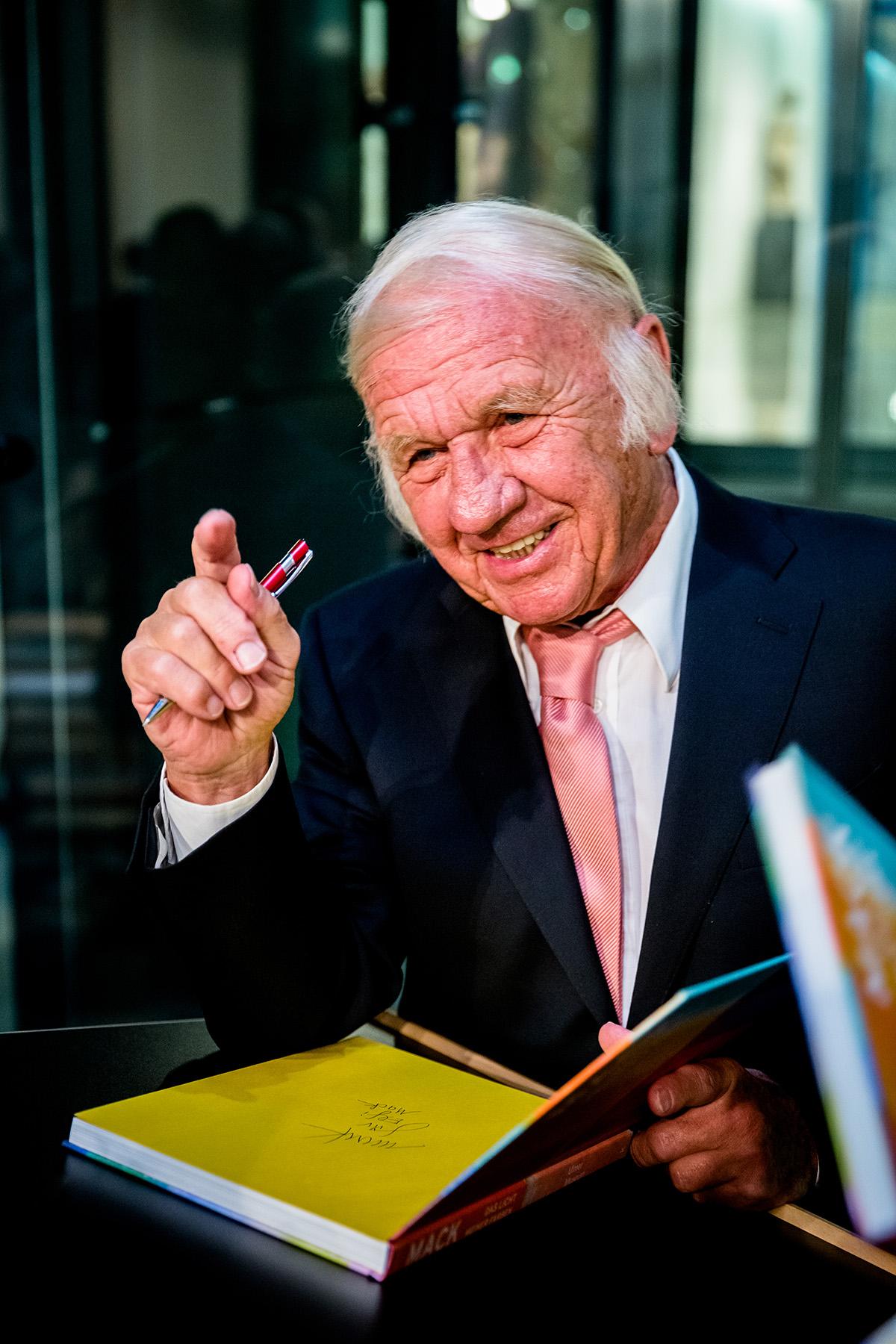 Zu sehen ist ein älterer Mann im Anzug. Vor ihm liegt ein Buch, welches er gerade signieren möchte.